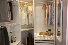 12 a small farmhouse closet with holders for hangers, shelves with boxes, built-in drawers, a wooden stool and a whitewashed ceiling