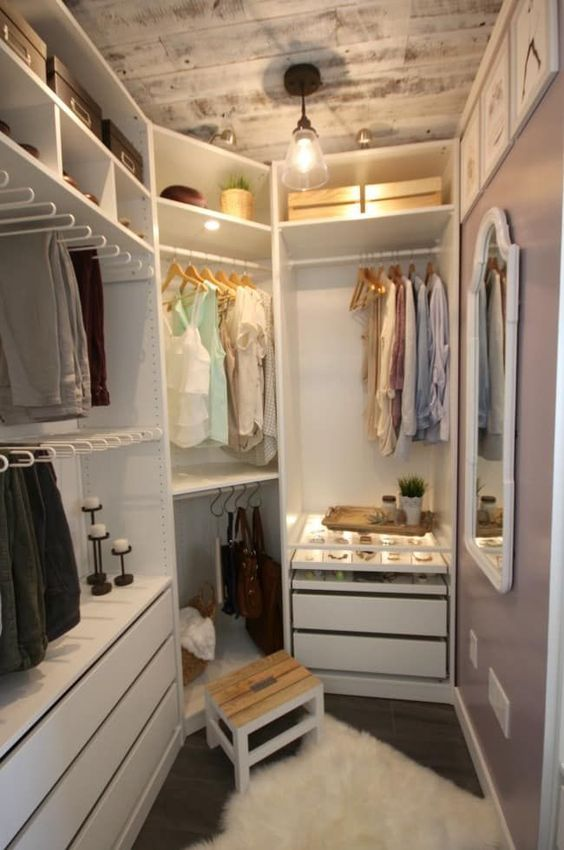 a small farmhouse closet with holders for hangers, shelves with boxes, built-in drawers, a wooden stool and a whitewashed ceiling