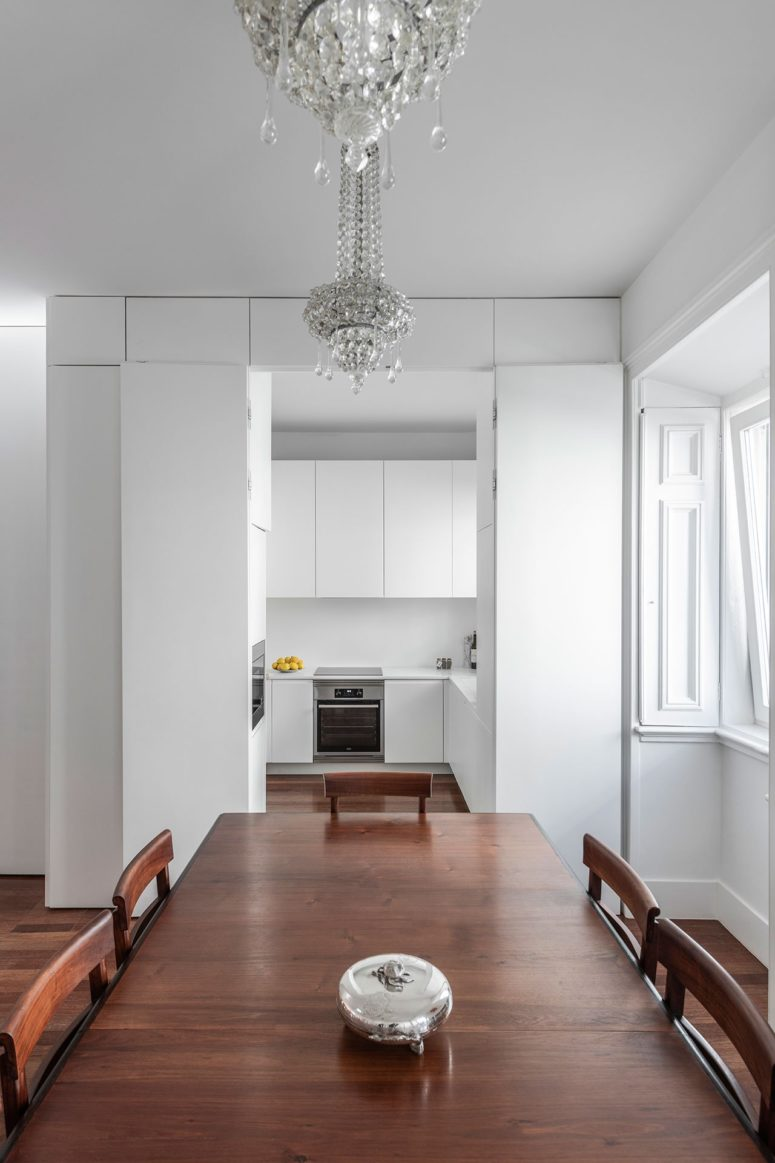 This kitchen is pure white and sleek, it's small yet very functional