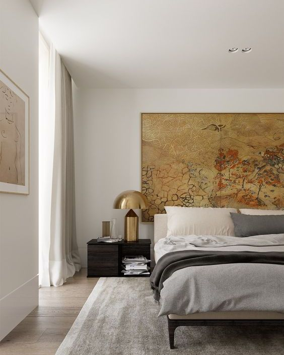 a chic and stylish bedroom with a statement artwork and bold brass lamps that add chic and a cool look to the space