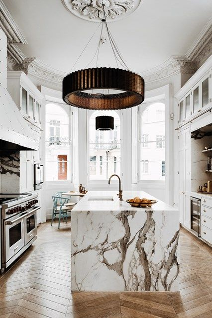 a luxurious white kitchen with a large kitchen island and a fantastic white marble countertop that wows at once