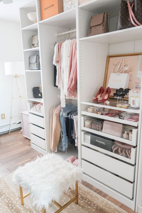 a small glam closet with holders and hangers, built-in drawers, open shelving, artworks, a faux fur stool and a printed rug