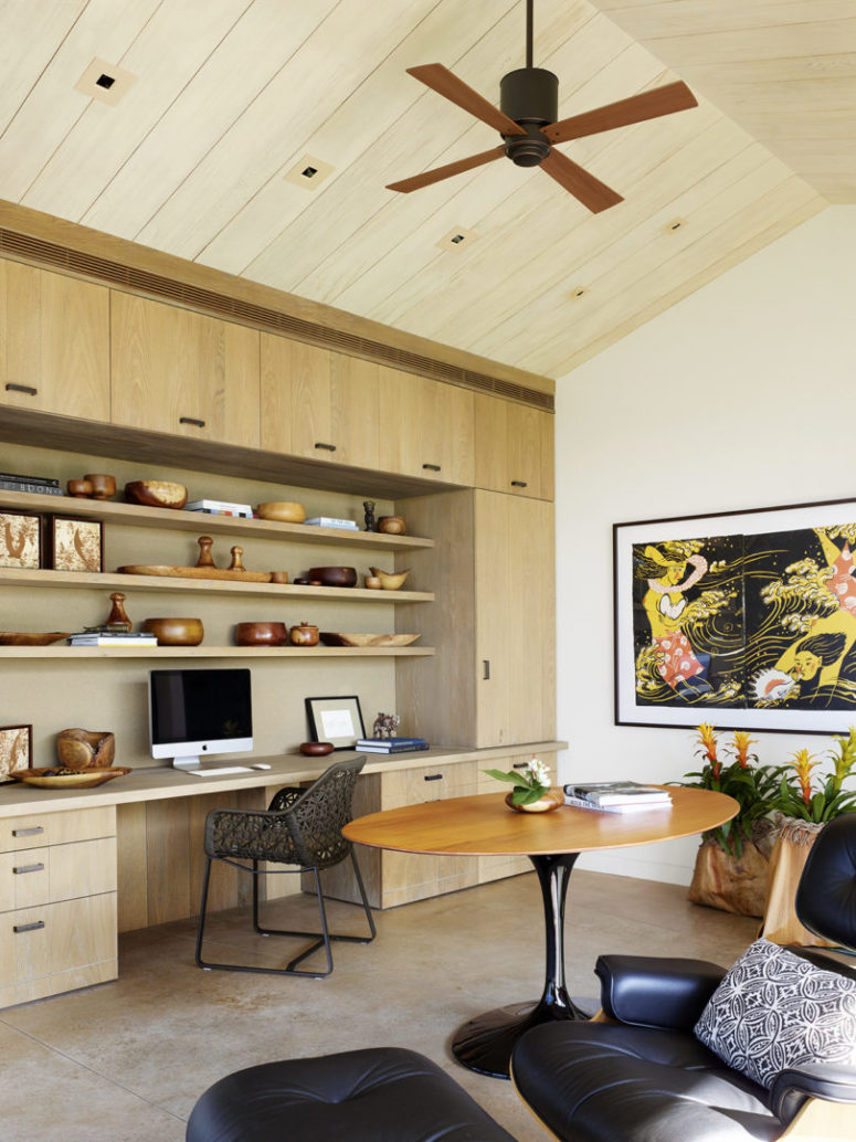 The home office features a built-in desk and shelves and cool wooden art and accessories