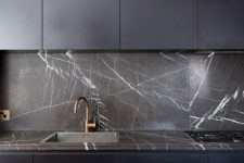 14 a minimalist midnight blue kitchen with a black marble backsplash and countertop that give it an ultimate luxe look and feel