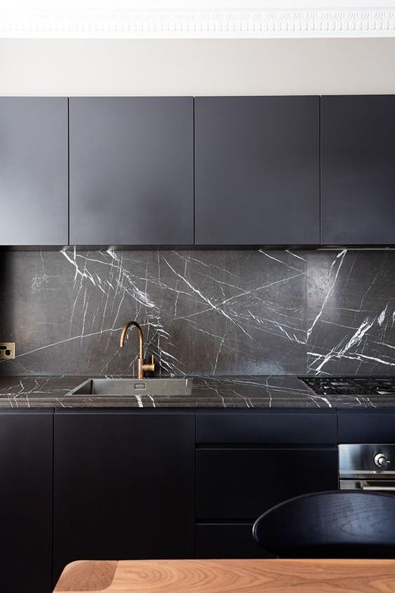a minimalist midnight blue kitchen with a black marble backsplash and countertop that give it an ultimate luxe look and feel