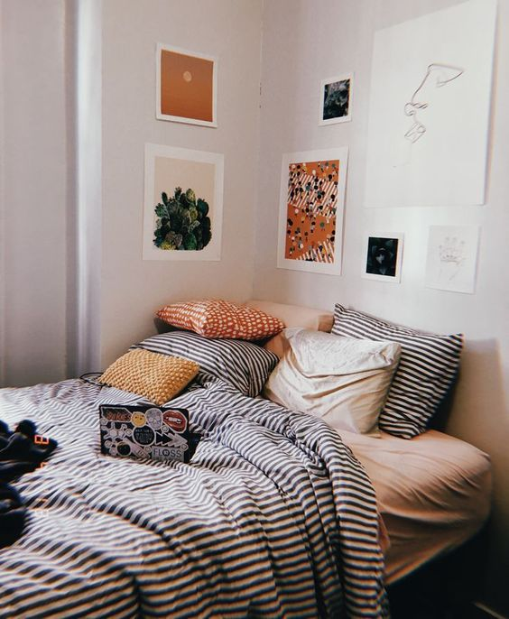 a pretty and bright gallery wall that hangs over the bed instead of a headboard and continues to the next wall