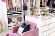 14 a small glam closet with lots of holders with hangers, shelves and drawers, a large dresser and a pink chair