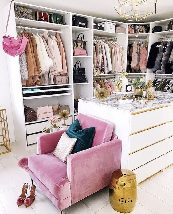 a small glam closet with lots of holders with hangers, shelves and drawers, a large dresser and a pink chair