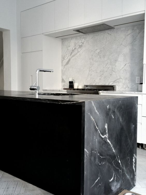 a minimalist white kitchen and a black kitchen island with a cool black marble countertop that echoes with a white marble backsplash