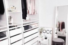15 a small glam closet with shelves, a holder for hangers and some drawers, a large window and a cute suede ottoman
