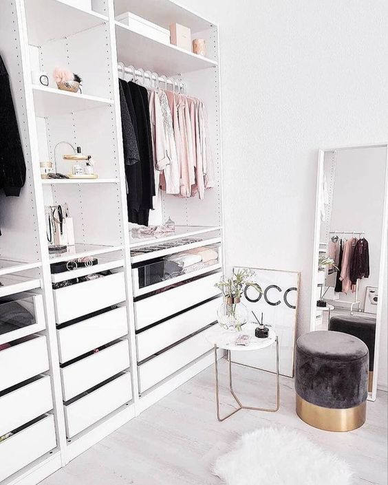 a small glam closet with shelves, a holder for hangers and some drawers, a large window and a cute suede ottoman