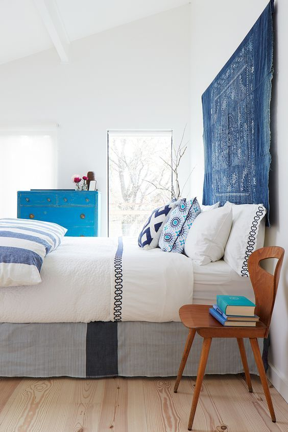 a bold and vivacious bedroom in white, with printed and colorful textiles, a blue tapestry instead of a usual headboard