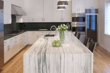 16 a monochromatic kitchen with a gorgeous kitchen island that features a white marble countertop and makes a statement