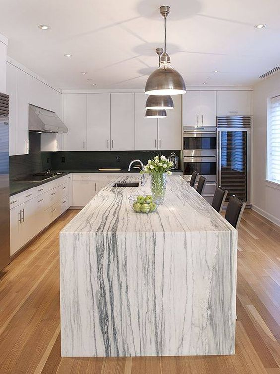 a monochromatic kitchen with a gorgeous kitchen island that features a white marble countertop and makes a statement
