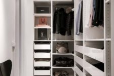 16 a small minimalist closet with holders for hangers, lots of drawers, open shelves and a single black chair
