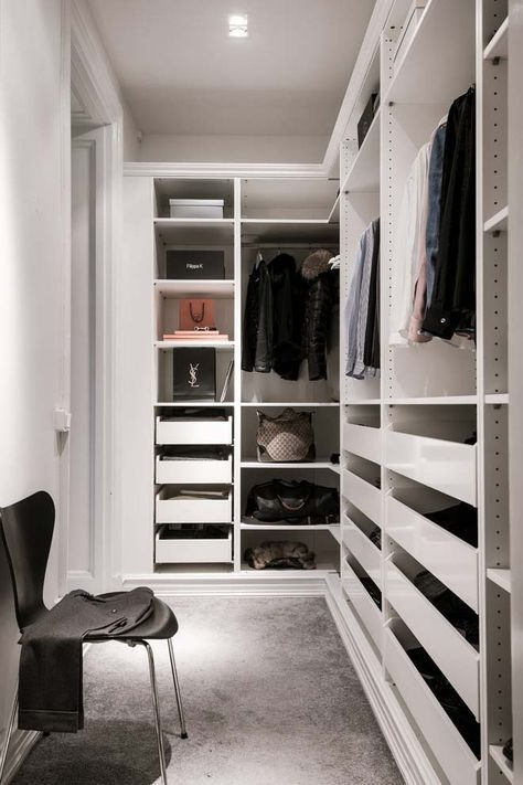 a small minimalist closet with holders for hangers, lots of drawers, open shelves and a single black chair