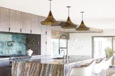 18 a neutral wooden kitchen with a large kitchen island topped with a gorgeous stone waterflal countertop that brings a luxurious feel