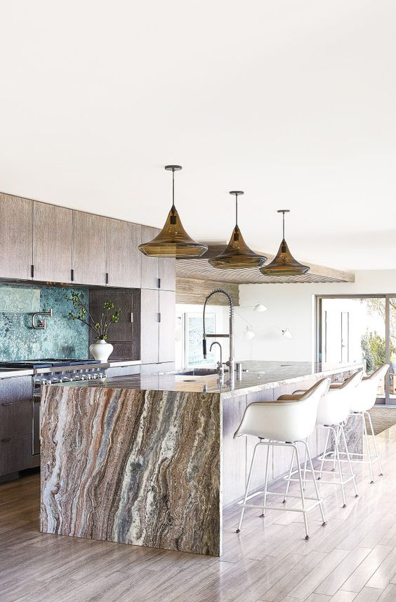 a neutral wooden kitchen with a large kitchen island topped with a gorgeous stone waterflal countertop that brings a luxurious feel