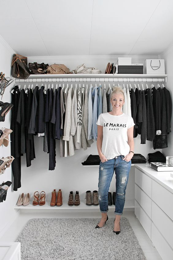 a small Scandinavian closet with open holders for clothes hangers, some shelves, shoe racks on the wall and dressers by IKEA