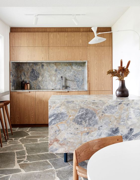 a small light-colored kitchen with a grey marble backsplash and countertops including a waterfall one that rocks