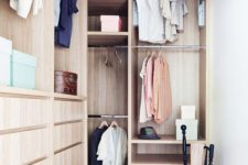 20 a small stylish closet done in light stained wood, with holders for clothes hangers, some open shelves, built-in drawers and a black chair