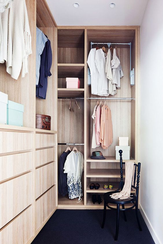 a small stylish closet done in light stained wood, with holders for clothes hangers, some open shelves, built-in drawers and a black chair