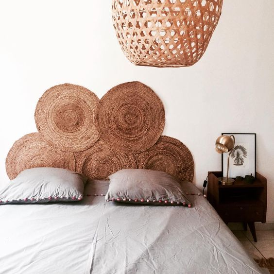 a stack of jute rugs, a wicker lamp make the bedroom feel more natural and more outdoor inspired