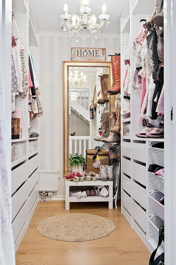 a small vintage-inspired sweet closet with a large mirror, a crystal chandelier, open shelves and holders plus drawers