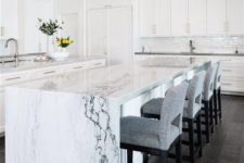21 an elegant white kitchen with a chic kitchen island with a white marble waterfall countertop that brings luxe here