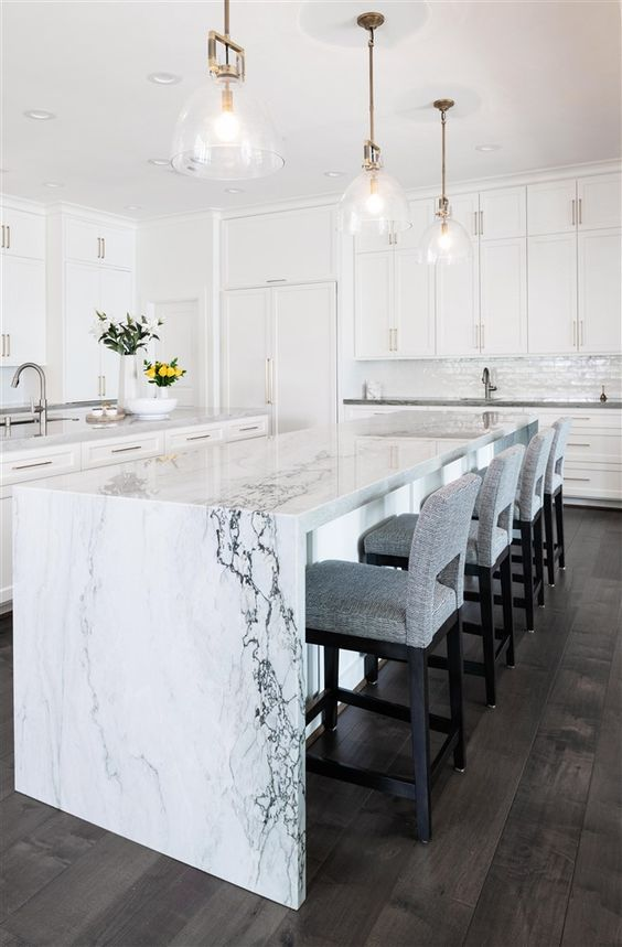 an elegant white kitchen with a chic kitchen island with a white marble waterfall countertop that brings luxe here