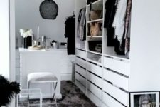 22 a small white closet with holders, shelves and lots of drawers, with a tiny table for makeup and a black pendant lamp