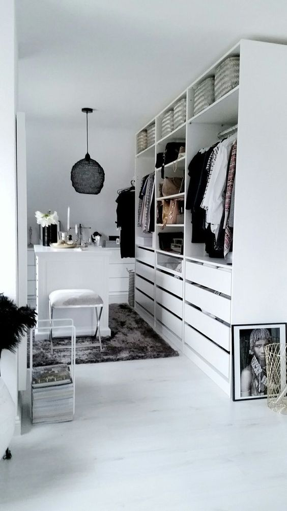 a small white closet with holders, shelves and lots of drawers, with a tiny table for makeup and a black pendant lamp