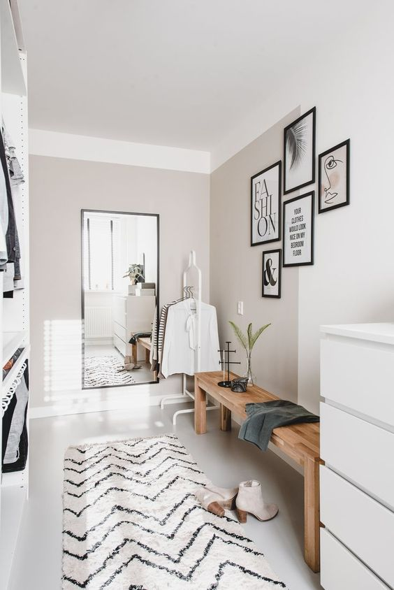 a small yet chic closet in neutrals, with a wooden bench, a mirror, a dresser, holders with hangers and a gallery wall