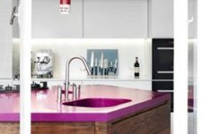 24 a sleek minimalist white kitchen and a dark stained kitchen island with a fuchsia countertop that makes a bold statement here