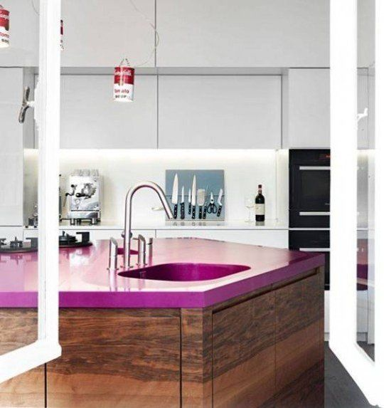 a sleek minimalist white kitchen and a dark stained kitchen island with a fuchsia countertop that makes a bold statement here