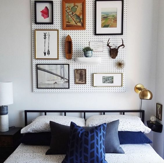 a white pegboard with artworks and potted greenery over the bed is a creative and cool alternative to a usual headboard
