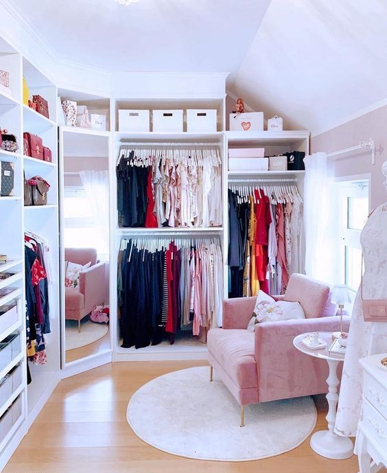 a tiny cute closet with lots of clothes on hangers, some drawers for small stuff and accessories and shelves for bags plus a pink chair
