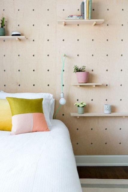 a pegboard wall with various shelves, potted blooms and greenery and even a bulb attached for more functionality