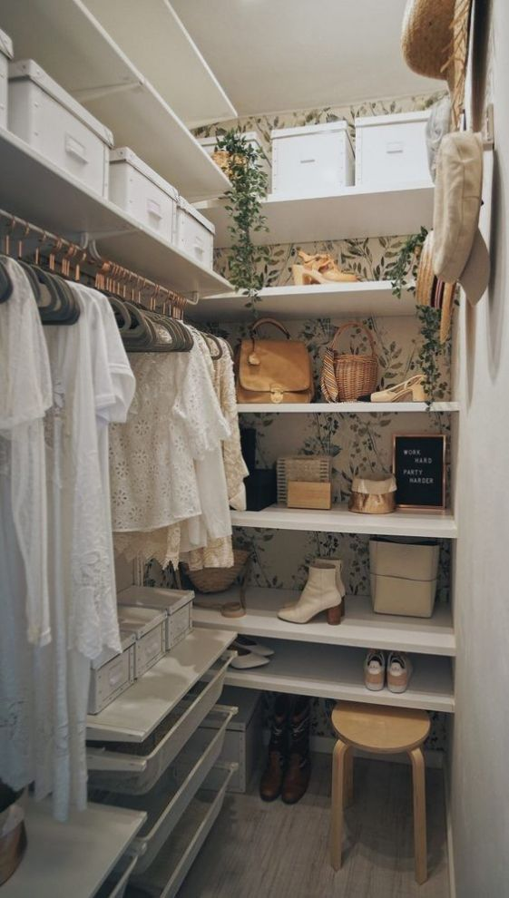a tiny girlish closet with botanical wallpaper, a faux cascading plant, open shelves, some cubbies, holders for hangers and a wooden stool