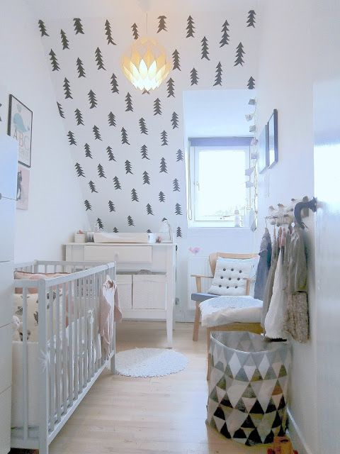 a Nordic nursery with a fir tree wall, a black and white can, neutral furniture and some artworks for an ambience
