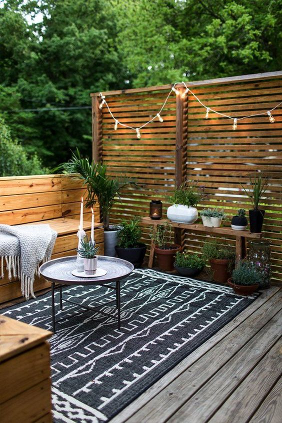 a Nordic patio all clad with wood, with a printed rug, some potted greenery and candle lanterns and lights