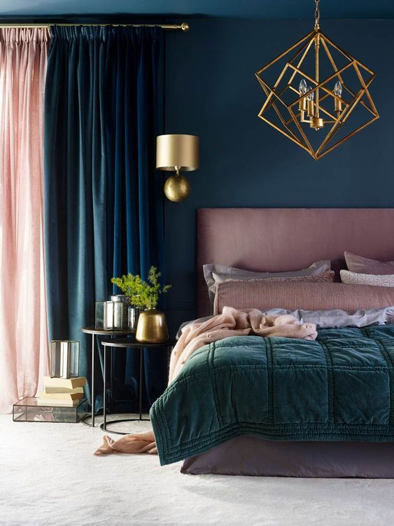 a beautiful bedroom in teal and dusty pink, with a pink bed and bedding, a gold chandelier and sconces for a wow look