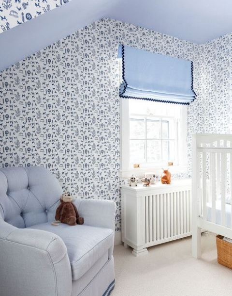 a blue cottage nursery with wallpaper walls, blue textiles and upholstery plus white furniture