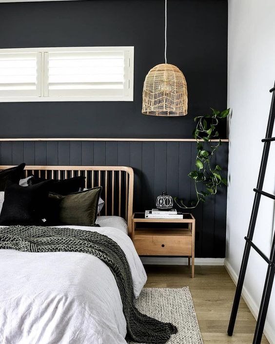 a boho bedroom with a black statement wall done with beadboard, wooden items, comfy layered textiles and greenery