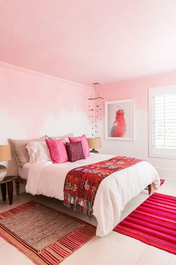 a bold bedroom with ombre pink walls, a pink ceiling, hot pink pillows and a rug plus a parrot artwork