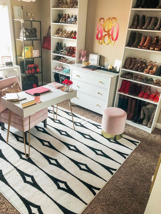 a bold glam home office with layered rugs, a small desk, a pink chair and ottoman, shoe and bag racks