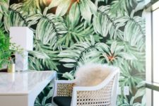 a bold tropical home office with an accent wall, leather chairs, touches of gold and brass and greenery
