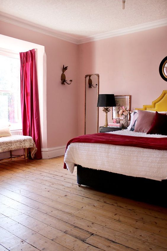 a bold whimsical bedroom with pink walls, fuchsia curtains, statement pillows, a black bed and lamps