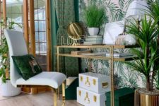 a bright and glam tropical home office with an accent wall, green and white boxes, a gold glass desk, brass planters and a glam chair