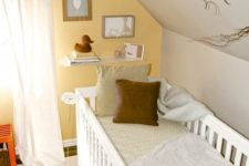a bright attic nursery with a yellow accent wall, cozy textiles and a rug plus a small gallery wall and branches for a natural touch